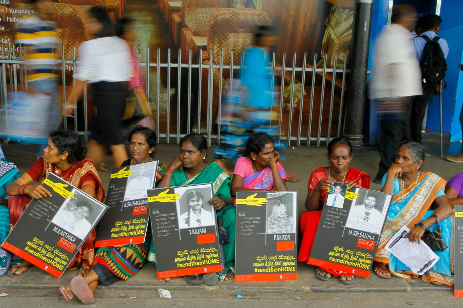 ** HOLD TO GO WITH STORY SLUGGED SRI LANKA SLOWLY HEALING BY KRISHAN FRANCIS**   FILE-In this Monday, April 6, 2015, file photo, Sri Lankan ethnic Tamil women sit holding placards with portraits of their missing relatives as they protest out side a railway station in Colombo, Sri Lanka. Seven years since the end of a brutal civil war, Sri Lanka faces the daunting twin challenges of uniting ethnic communities polarized due to decades of acrimony and violence while also dealing with the divisive issue of addressing war crimes allegations. (AP Photo/Eranga Jayawardena, File)